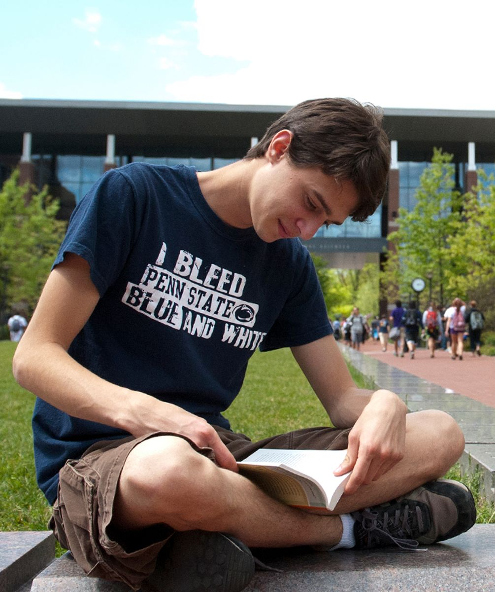 Penn State student studying outside in the Life Sciences Building.